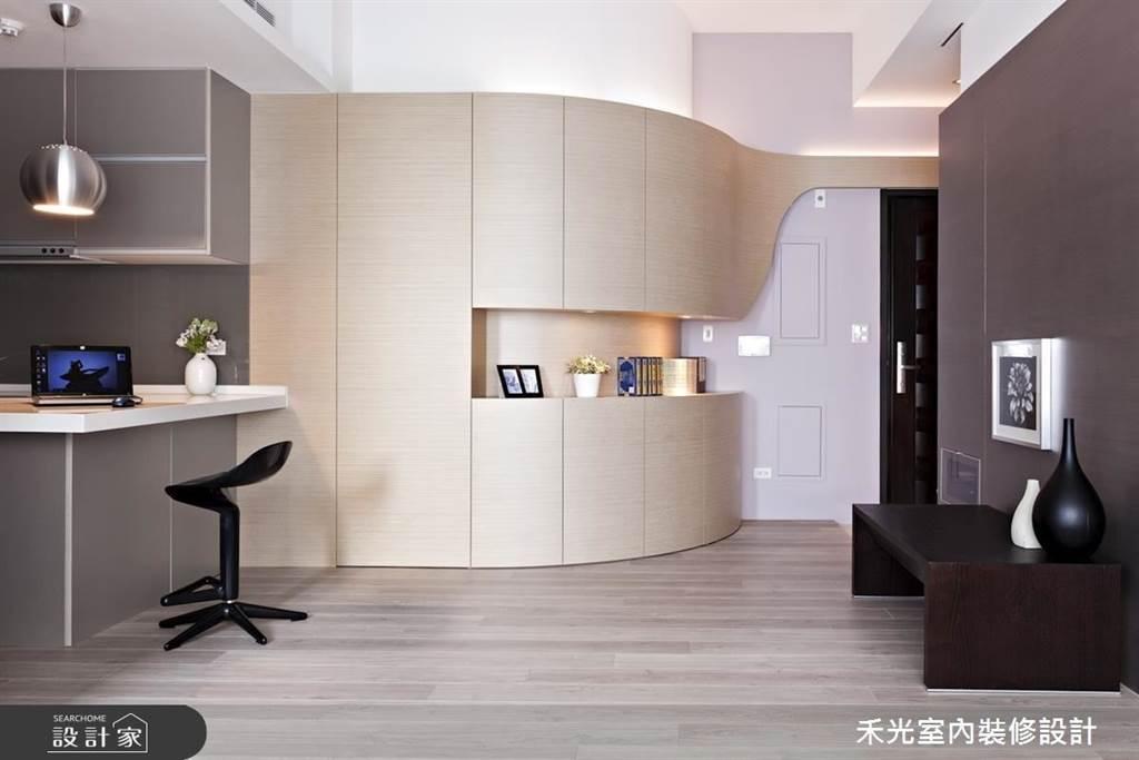 弧面造型的玄關收納向內引導著生活動線,中段凹槽設計讓櫃體變得活潑,也能放置屋主喜愛的書籍和展示品。(圖片提供/禾光室內裝修設計)