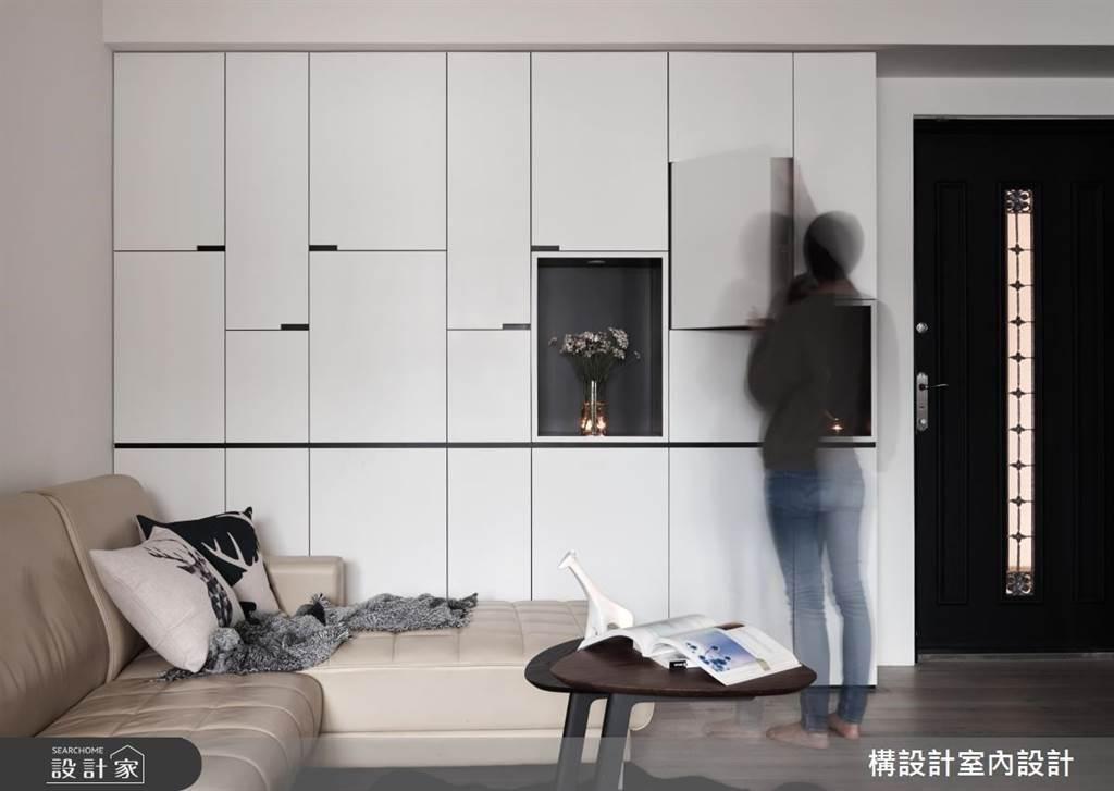 一進門就是客廳的15坪中古屋,在入門的牆面規劃白色系統櫃,提供鄰近的場域專屬的收納空間;線條切割與凹槽設計讓櫃體不只是收納,也是一面居家端景。(圖片提供/構設計室內設計)