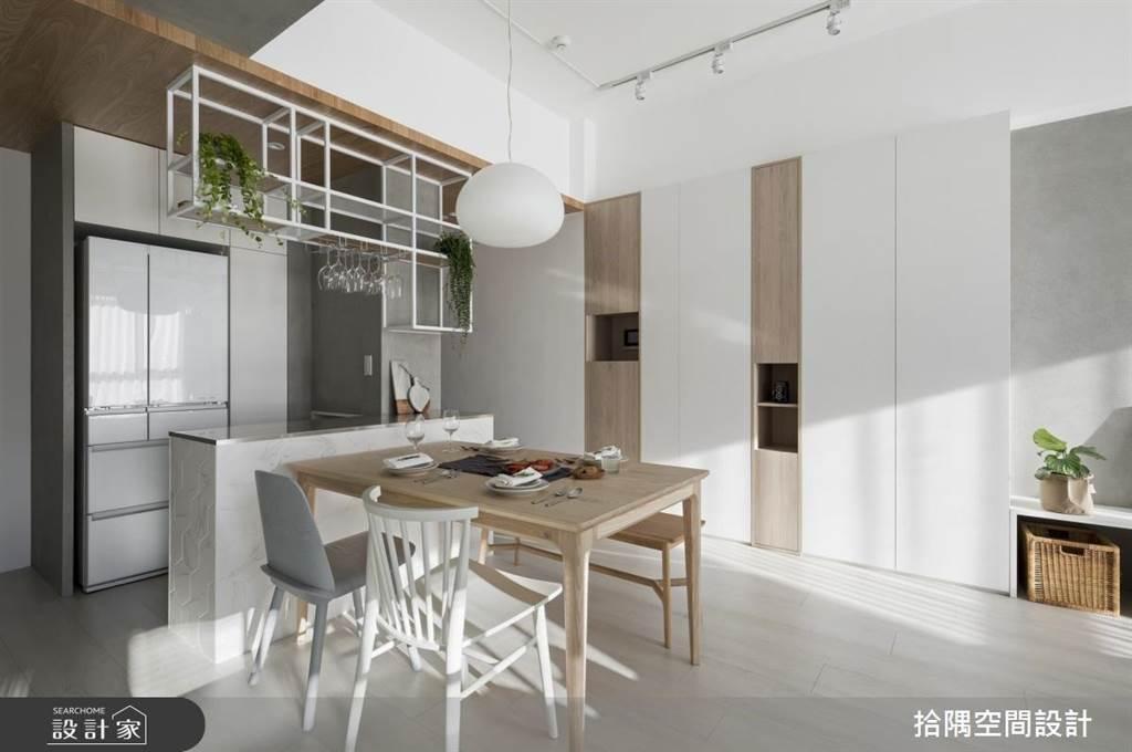 透過開放式餐廚的規劃順勢界定出對牆的機能,白色與淺木交錯排列的玄關櫃讓20坪的簡約空間能將鞋子收好收滿,讓家中呈現一片清爽簡潔。(圖片提供/拾隅空間設計)