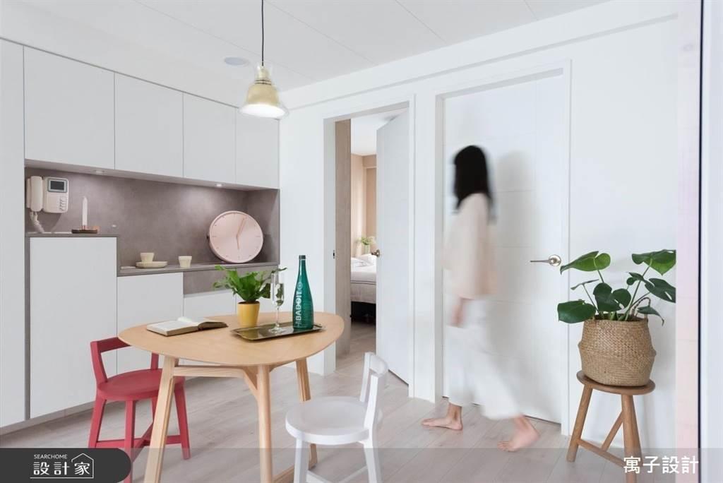 為了讓沒有玄關的空間也能有完備的收納機能,在入門的左側牆面將餐櫃與玄關櫃整合在一起,上下櫃設計提供長型置物平台,階梯狀下櫃設計輕量化整體,舒緩小空間的視覺壓力。(圖片提供/寓子設計)