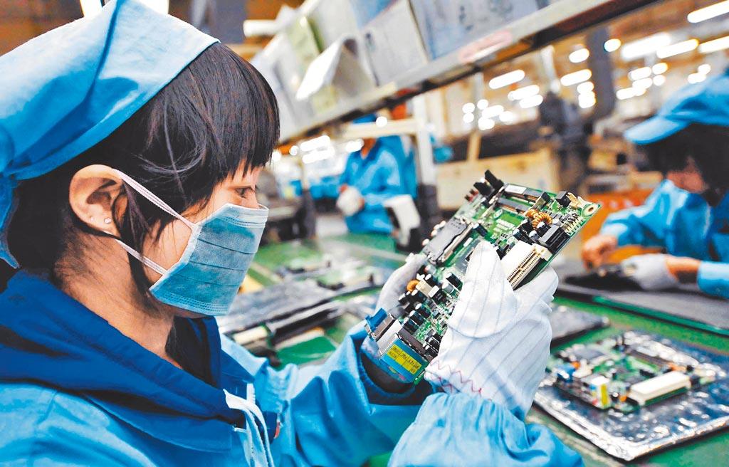 在中美貿易戰與新冠疫情下,供應鏈日趨分散。圖為一位女工在檢查電腦主板產品。(新華社資料照片)