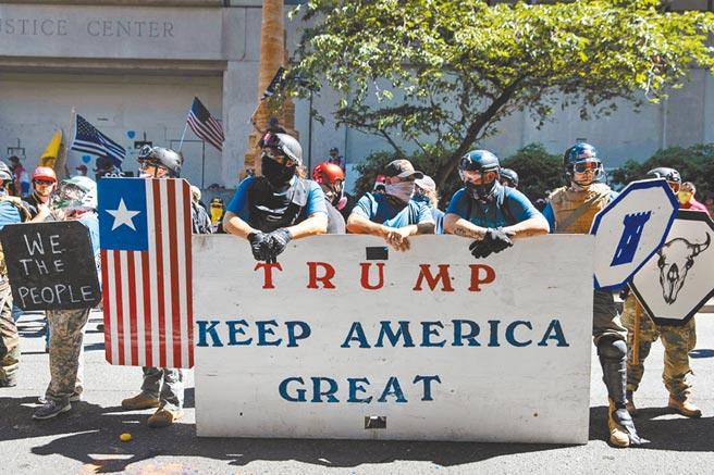 一群支持美國總統川普與警察的鐵粉,22日在奧勒岡州波特蘭的反種族主義示威中,舉國旗和挺川普標語反制。(路透)