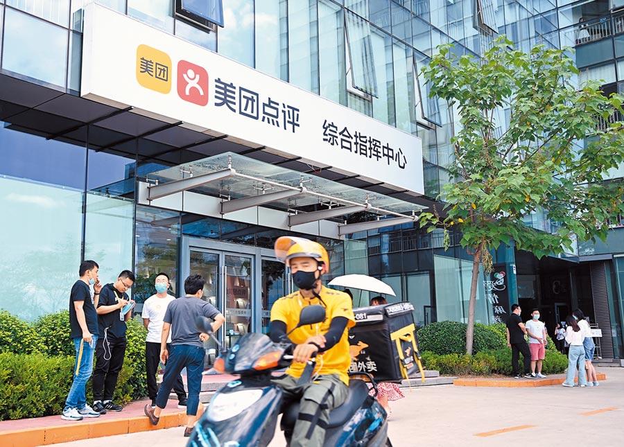 一名美團外送員經過美團點評公司北京總部的綜合指揮中心門口。(中新社資料照片)