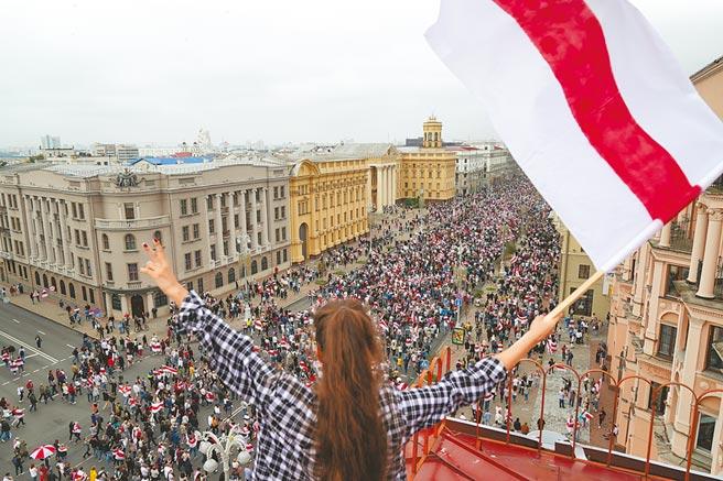 白俄羅斯首都明斯克23日再度爆發大規模示威,抗議人士徒步走到獨立廣場集結。圖為一名女子在樓頂揮舞紅白旗幟表達支持抗議。(美聯社)