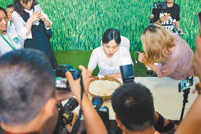 2016年8月2日,杭州市舉辦的「百人生擼白米飯」活動上,大胃王密子君線上直播狂吃白米飯。(中新社)