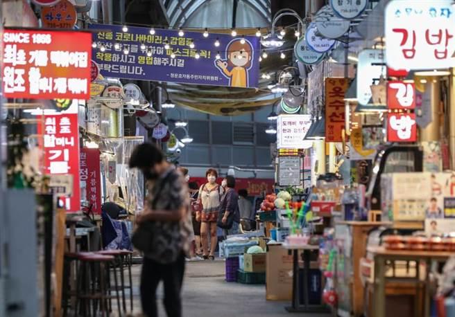 南韓首都圈疫情持續嚴峻,圖為8月25日,南韓首爾通仁傳統市場內懸掛有要求人們佩戴好口罩再營業的條幅。(新華社照片)