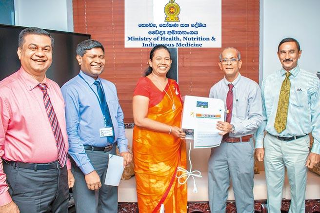 斯里蘭卡國家衛生部長瓦尼亞拉奇(Pavithra Wanniarachchi,中間)於斯里蘭卡國家奧委會秘書長迪席瓦(Maxwell de Silva,右二)手中接收了旺旺集團旗下水神的防疫物資。圖/旺旺集團提供