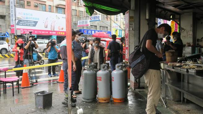 員林市永和豆漿店上午發生火警意外,盧姓負責人(中)低頭看著瓦斯桶不發一語。(圖/記者謝瓊雲攝影)