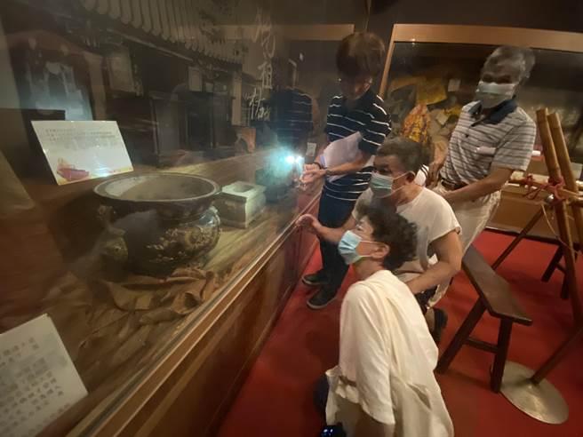 當年大甲東陶「內窯」會做香爐的師傅很少,竹南蛇窯已故窯主林添福就是其中之一,第二代窯主林瑞華、鄧淑慧夫婦,仔細觀察「獅耳團龍紋陶香爐」,希望確認香爐文物是否出自於老窯主林添福之手 。(巫靜婷攝)