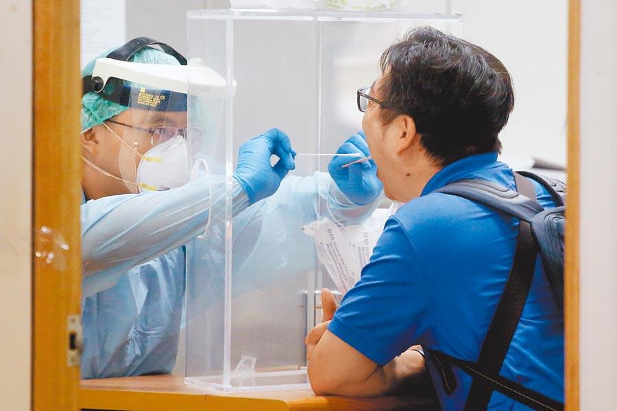 9月1日起機場入境旅客採檢新冠肺炎病毒時,不需再忍受插喉之苦,只要用唾液檢驗即可。圖為以往入境台灣旅客接受採檢。(本報資料照片)