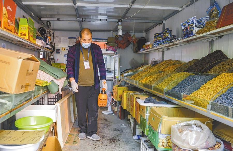 8月29日,新疆烏魯木齊市,一位經營乾果和水果的商戶在店內噴灑消毒液,準備開門營業。(中新社)