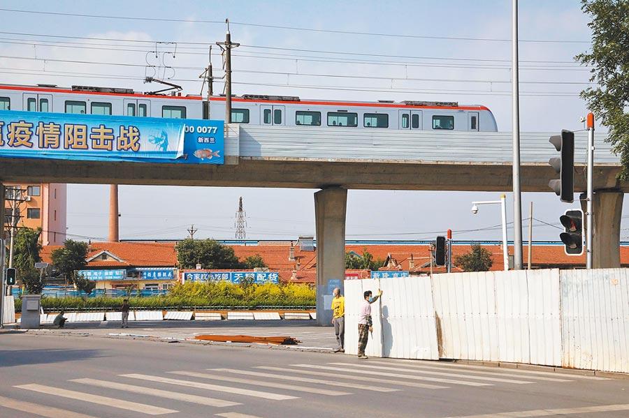 8月21日,新冠肺炎疫情好轉,大連地鐵3號線大連灣站解除封閉,工作人員拆除圍欄。(中新社)