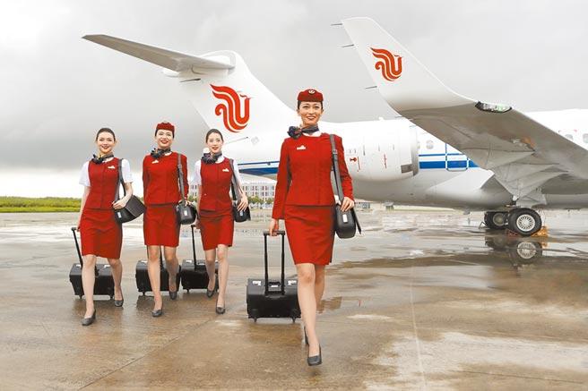 大陸三大航空上半年營收減半。圖為6月28日,國航乘務員在國航首架arj21客機前合影留念。(中新社)