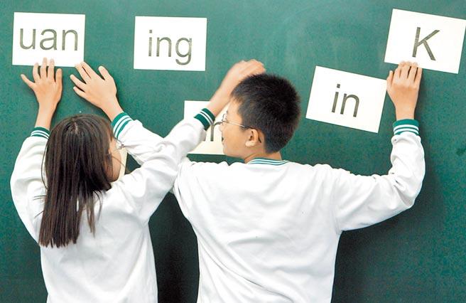 教育部長潘文忠堅持,111學年起將本土語文納入國高中必修課程。圖為老師以閩南語發音讓小朋友立即以羅馬符號拼出。(本報資料照片)
