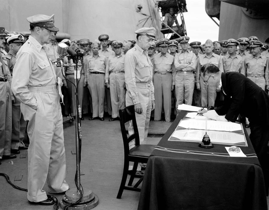1945年9月2日,密蘇里戰艦上的日本投降儀式,在麥克風旁的是麥克阿瑟將軍,椅子邊是參謀長理察·薩瑟蘭,彎腰簽字的是日本外相重光葵。(圖/美聯社)