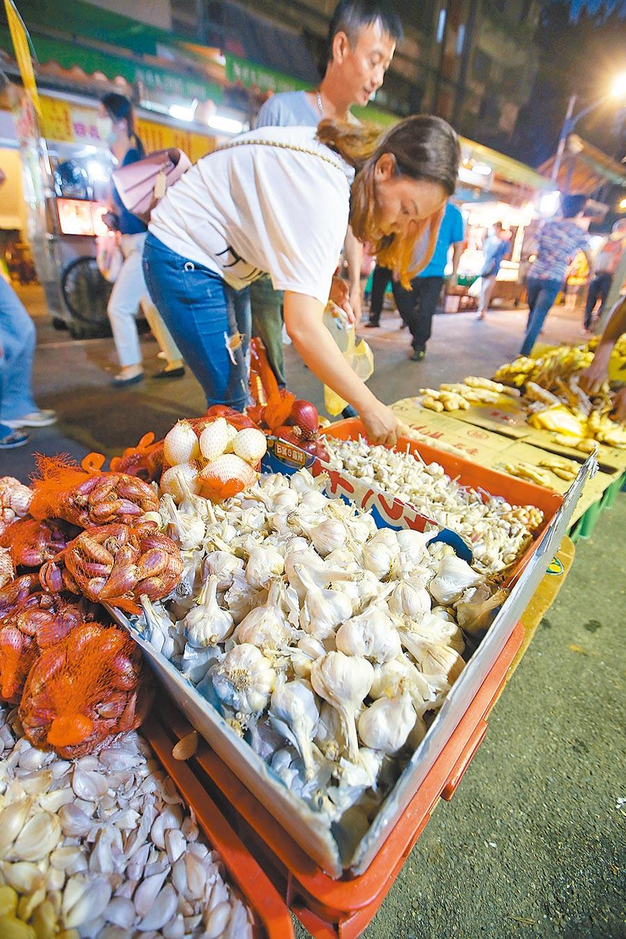 國內大蒜供不應求,攤商表示進貨價格已經由一斤100多元漲至200多元。圖為民眾選購蒜頭畫面。(陳信翰攝)