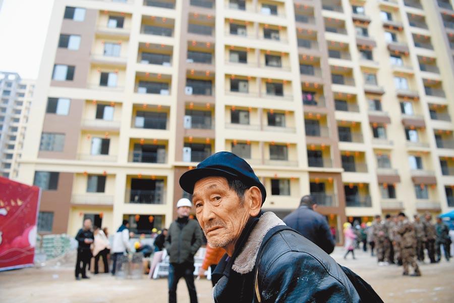 大陸一名老人在政府興建的安置房前駐足。(中新社資料照片)