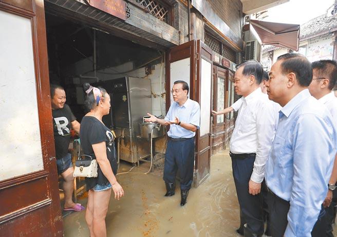 8月20日,大陸國務院總理李克強(左3)涉水赴重慶磁器口商業區,了解因疫情和水災造成的商家損失。(新華社)