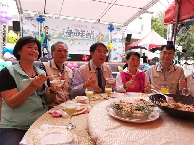 台南七股海鮮節七寶宴5日於七股國小戶外辦桌,台南市長黃偉哲(中)也到場大啖美食。(劉秀芬攝)