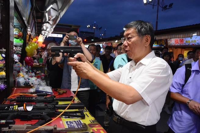 柯文哲對於夜市店家遊戲頗為好奇,當場玩起BB槍。(王志偉攝)