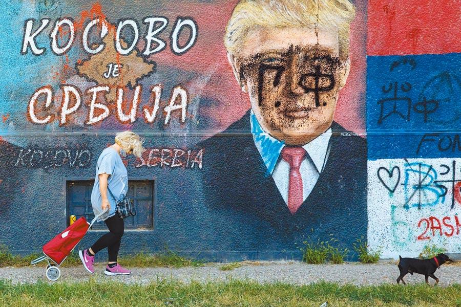 塞爾維亞首都貝爾格勒,一名婦人和一隻小狗4日步行經過一幅描繪美國總統川普的壁畫,壁畫上寫著:「科索沃是塞爾維亞的」。在美國斡旋下,塞爾維亞與科索沃4日同意經濟關係正常化。(路透)