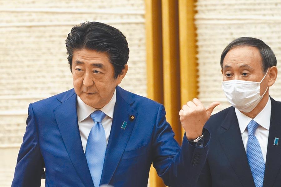 菅義偉(右)表示一旦擔任首相將繼續執行安倍(左)的政策。(美聯社)