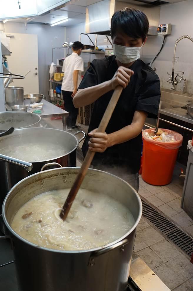 〈鐵火肥牛火鍋〉廚房內有一不鏽鋼大桶,熬煮著稠濃且味道極鮮的「老火雞湯」供客人作為啖鍋的湯底。(圖/姚舜)