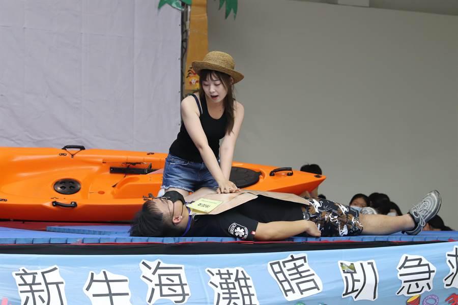 穿著清涼帥哥辣妹學長姐,以海邊溺水急救的行動劇演出,指導學生如何在緊急關頭救人一命。(曹婷婷攝)