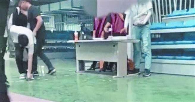 和碩子公司昆山世碩電子將員工證件丟在地上,新員工須彎腰去撿。(圖/截圖自微博@鯨視頻)