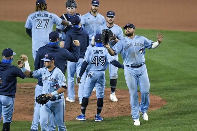 藍鳥隊單局得10分大逆轉擊敗洋基隊,球員相互擊掌慶祝勝利。(美聯社)