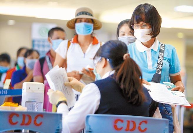 中央流行疫情指揮中心7日公布,新增1例新冠肺炎境外移入確診病例。圖為一群旅客在入境前查驗健康聲明書。(本報資料照片)