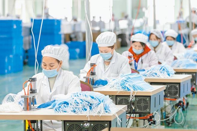 上海浦東的三槍工業城工廠內,工人生產準備出口的口罩。(新華社資料照片)