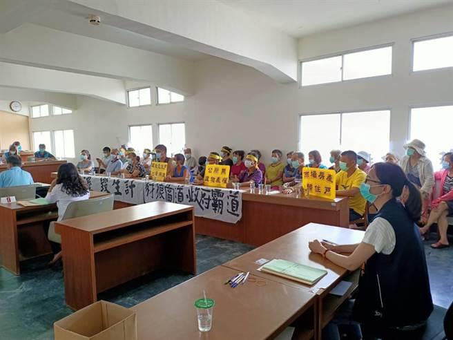 20多位民眾聚集臨時會現場,舉牌抗議堅決反對搬遷,要求撤回提案。(張毓翎攝)