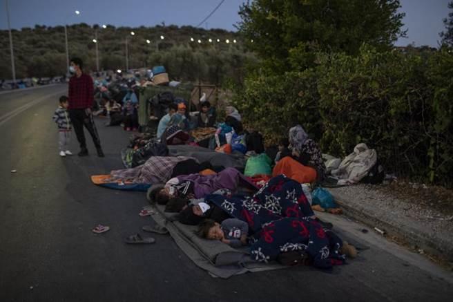 難民營遭燒毀後,難民被迫在道路,田野間和停車場就地睡覺休息。(美聯社)