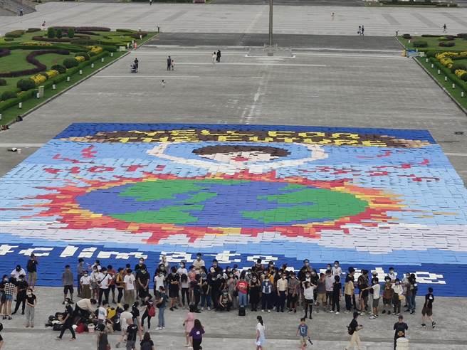 上百位高中、大學青年今天與綠色和平今天排出大型藝術拼圖,希望傳遞年輕世代呼籲各界關注氣候緊急狀態。(林良齊攝)