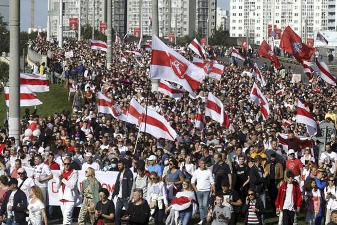 9月13日,白羅斯反對派群的集會遊行,抗議者手持白羅斯舊國旗遊行,抗議明斯克的正式總統選舉結果。(圖/美聯社)