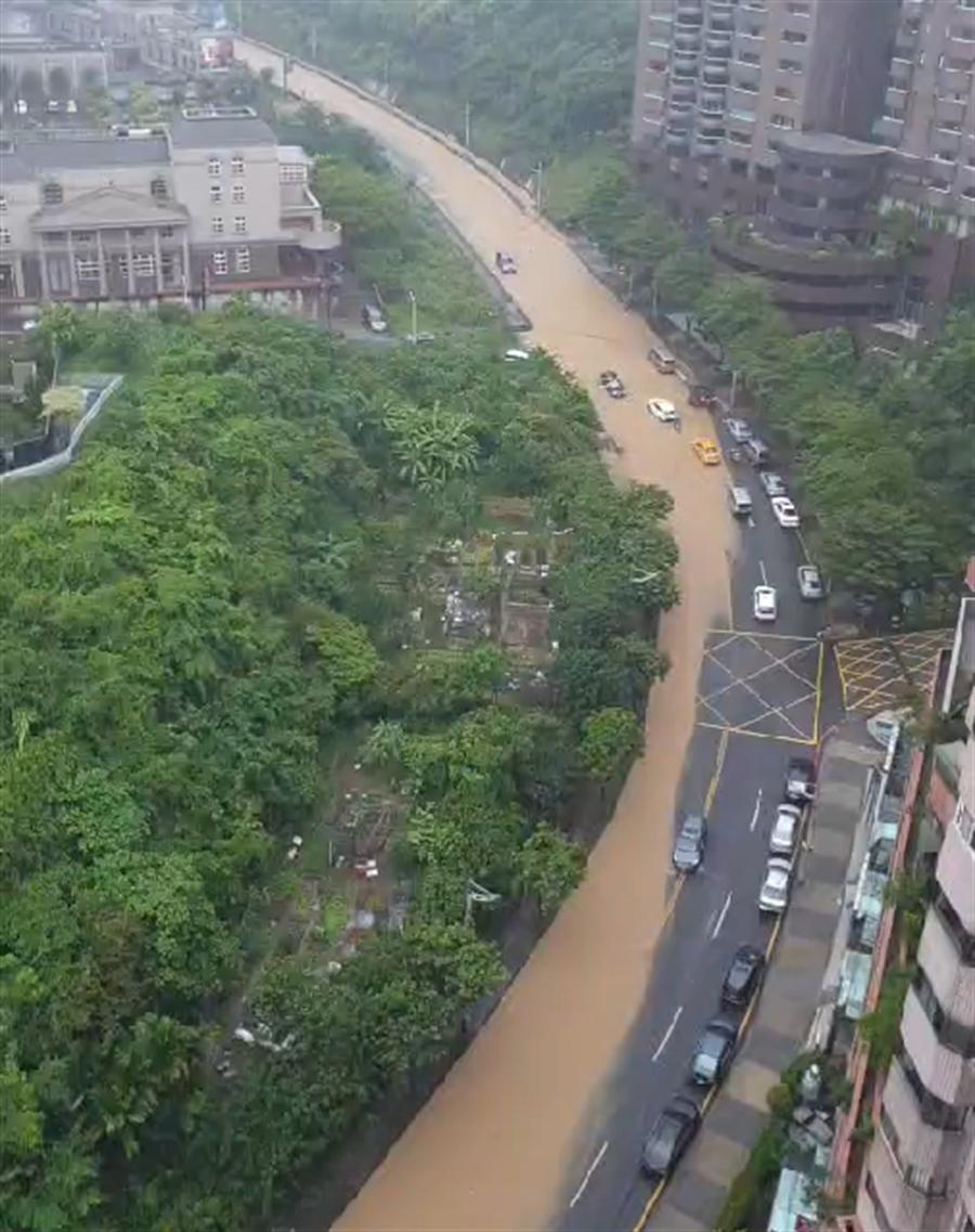 基隆樂利三街與基金一路大淹水,整條路快被充滿泥濘的雨水淹沒。(翻攝照片/陳彩玲基隆傳真)