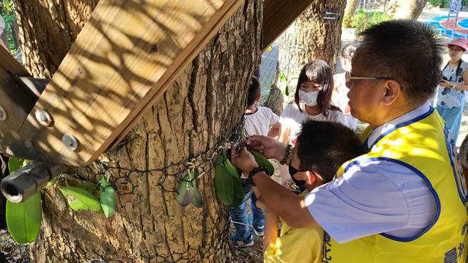 員林東北扶輪社社長張嘉六(右)帶領社友與眷屬們,陪著孩子們一起種下一棵棵的蝴蝶蘭。(謝瓊雲攝)