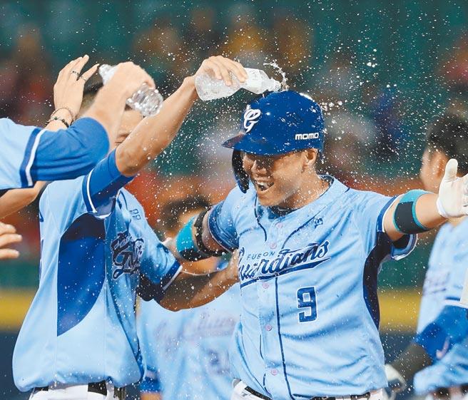 9局下林益全(右)擊出再見安打,隊友衝入場中對他澆水慶祝。(陳怡誠攝)