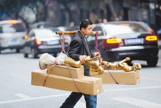 重慶一名「棒棒軍」(搬運工,多為年齡偏大的農民工)在車陣中運送貨物。(中新社資料照片)