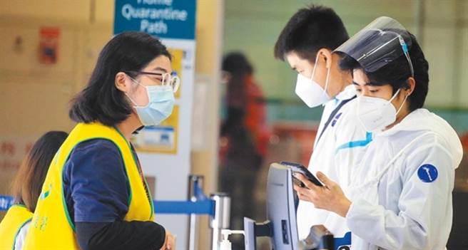 圖為桃園機場入境管制區內,2名身穿防護衣、從菲國搭機抵台的旅客,正在查驗健康聲明書。(資料照片 范揚光攝)