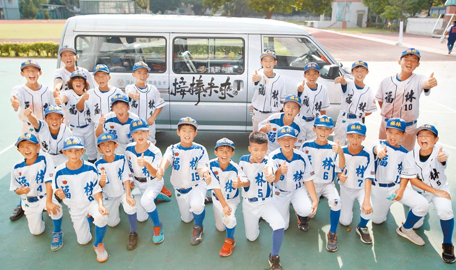 台北市6所學校棒球隊獲頂新和德文教基金會贈送交通車,福林國小少棒隊員高興的在嶄新的交通車旁比讚。(鄭任南攝)