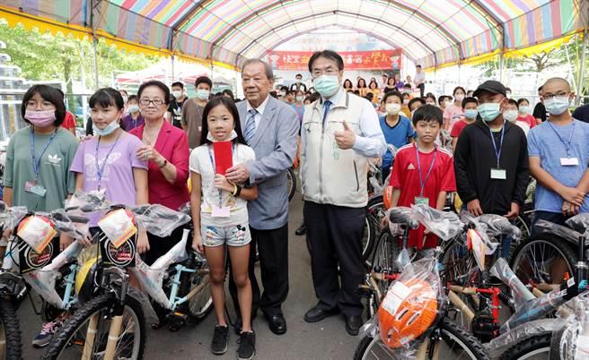 「康那香」董事長戴榮吉(左五)為紀念父親成立「戴竹基金會」,長期助學,每年都會捐單車、書包文具、助學金給國中小新生,已經13年不間斷,累積金額超過2000萬元。