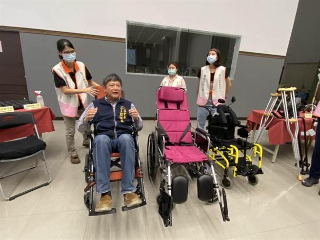 台中市社會局18日在市府內打造小型輔具中心,社會局長彭懷真體驗輪椅與助行器。(盧金足攝)