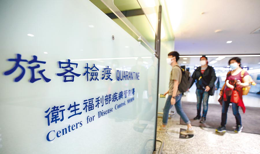 中央流行疫情指揮中心11日公布,國內新增2例新冠肺炎境外移入病例,一群旅客11日搭機抵達桃園機場,在入境前走過發燒篩檢站。(范揚光攝)