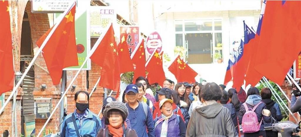 青天白日滿地紅國旗與大陸五星旗在金門模範街同步飄揚,吸引兩岸遊客來到。(圖/本報資料照,李金生攝)