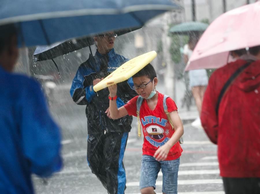 雷雨彈轟炸!北北基升級豪雨 北部5縣市豪大雨特報。圖為小朋友拿起浮板遮雨快跑過馬路。(資料照 陳信翰攝)