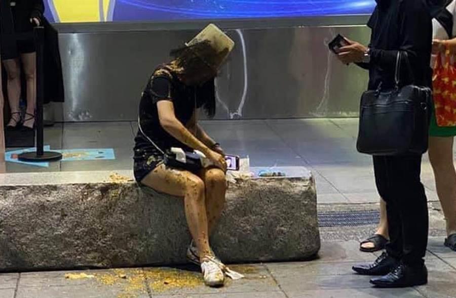 妙齡長髮女在北市信義區威秀廣場遭黑衣男當頭潑屎,路人也看傻。(截自臉書《爆料公社》)