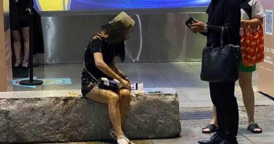 邱姓女子坐在信義區石椅上靚遭人持裝滿糞便的水桶倒蓋在頭上。(圖/翻攝畫面)