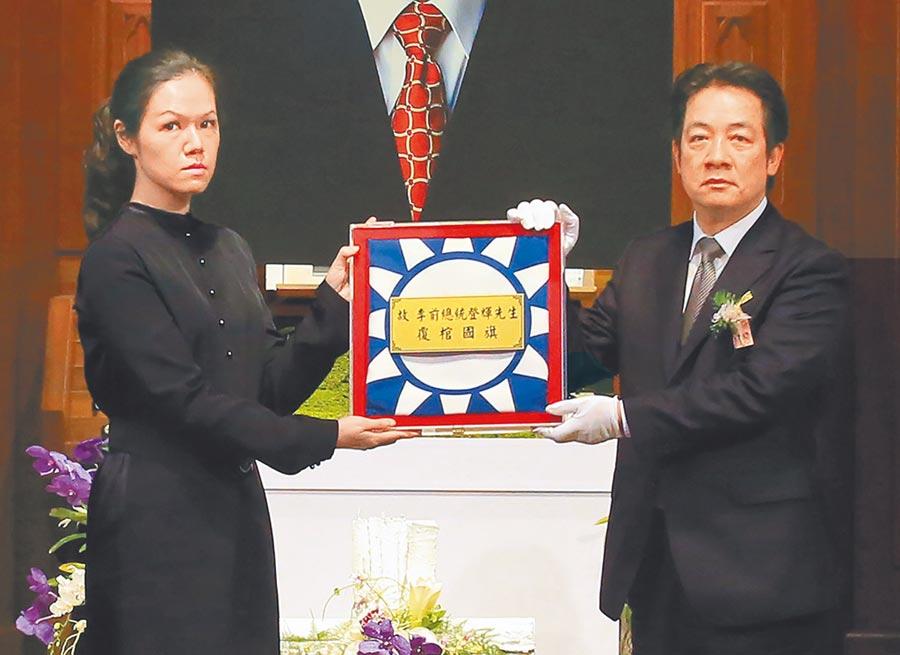 副總統賴清德(右)將覆棺國旗致贈家屬,由李登輝孫女李坤儀(左)代表接受。(台北市攝影記者聯誼會提供)
